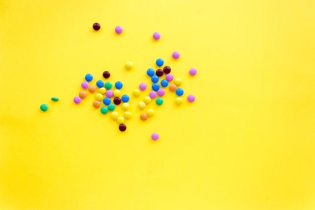 Piccole caramelle colorate, su fondo giallo