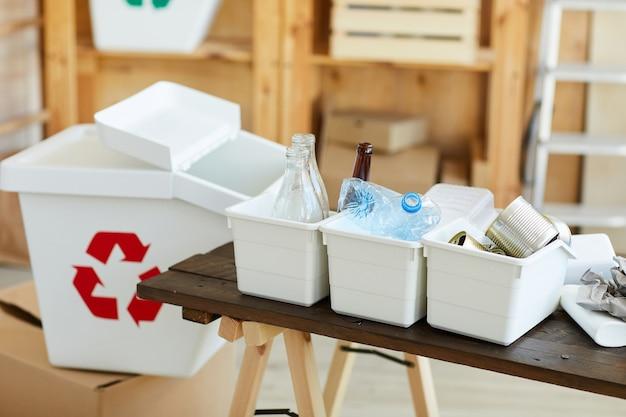 Piccoli contenitori con plastica spazzatura ordinata di vetro e lattine