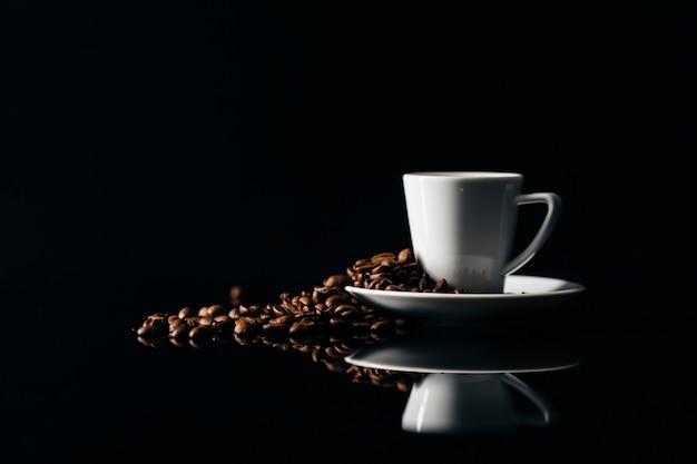 Piccola tazza di caffè nero su uno sfondo scuro con chicchi di caffè