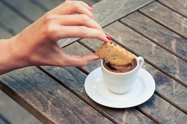 Piccola tazza di caffè espresso su un tavolo di legno. la mano femminile immerge un biscotto nel caffè.
