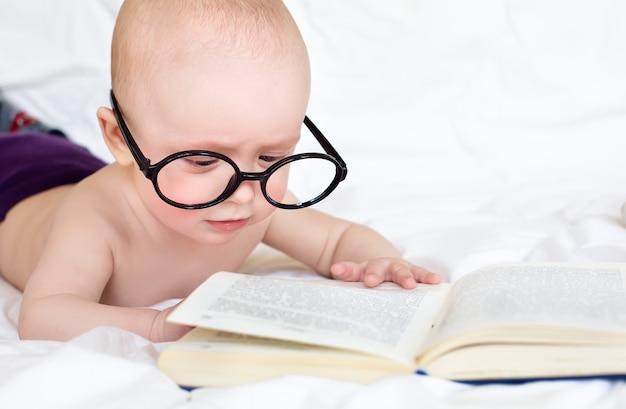 Piccolo bambino carino cerca di leggere un libro