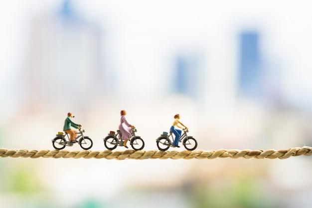 Piccole figure in bicicletta su corda con sfondi di città.