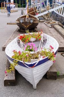 Piccola barca decorativa con fiori e piante all'interno.