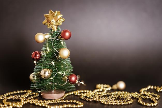 Piccolo albero di natale decorativo con giocattoli e una ghirlanda su sfondo nero con bokeh natale c...