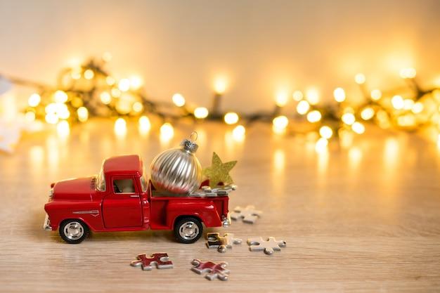 Piccola auto rossa decorativa di natale brillante in primo piano su uno sfondo sfocato di decorazioni natalizie, ghirlande e luci bokeh. foto di alta qualità