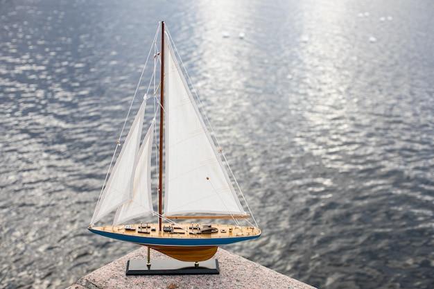 Piccolo modello in legno decorativo di uno yacht a vela sullo sfondo della piattaforma dell'acqua con copyspace