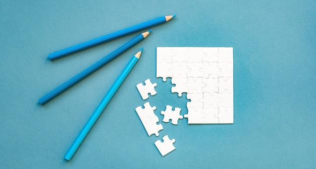 Piccolo puzzle quadrato bianco smontato e matite su un blu