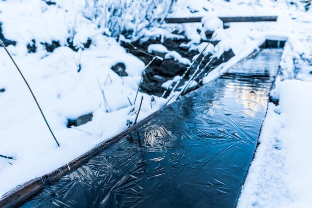 Una piccola sorgente veloce con acqua pulita, fresca e trasparente tra la neve pesante e la foresta scura nelle pittoresche montagne dei carpazi