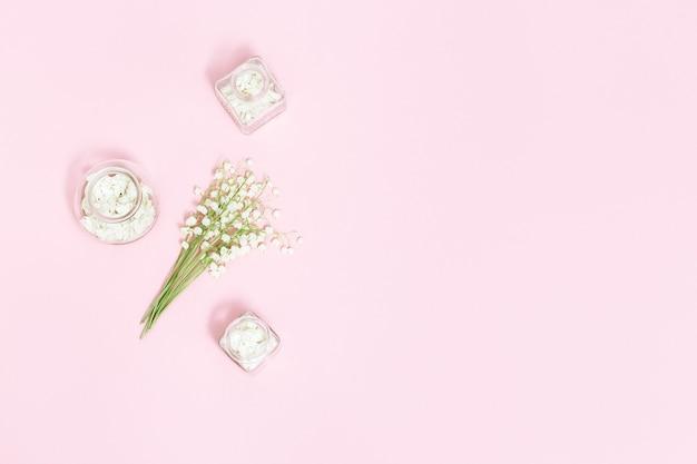 Piccoli primi fiori di primavera mughetti e bella bottiglia in vetro con petali essiccati per aromaterapia.