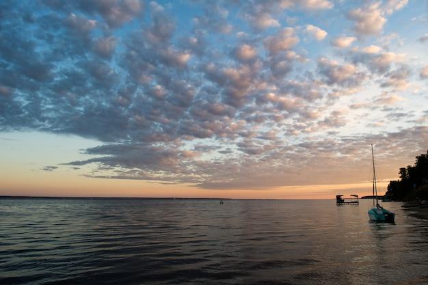 Piccolo peschereccio sulla spiaggia con il fondo di tramonto di mattina