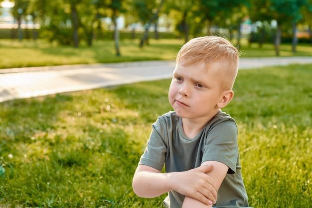 Un piccolo ragazzo dai capelli rossi di cinque anni che si tiene il gomito e pensa nel parco, primo piano