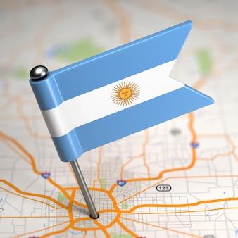 Piccola bandiera dell'argentina incollata sullo sfondo della mappa con il fuoco selettivo.