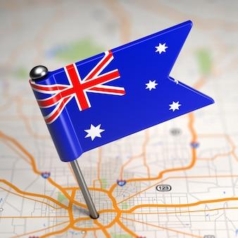 Piccola bandiera dell'australia su uno sfondo di mappa con il fuoco selettivo.