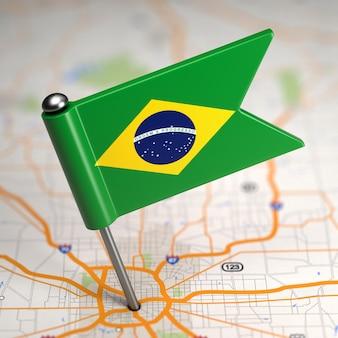 Piccola bandiera del brasile incollata sullo sfondo della mappa con il fuoco selettivo.