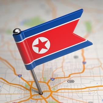 Piccola bandiera della repubblica democratica popolare di corea su uno sfondo di mappa con il fuoco selettivo.