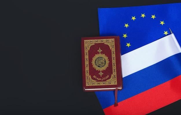 Piccola bandiera dell'ue e della russia e un agrifoglio del corano su una superficie di plastica nera