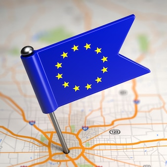 Piccola bandiera dell'unione europea su uno sfondo di mappa con il fuoco selettivo.