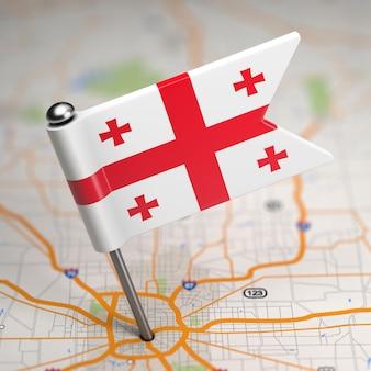 Piccola bandiera della georgia su uno sfondo di mappa con il fuoco selettivo.