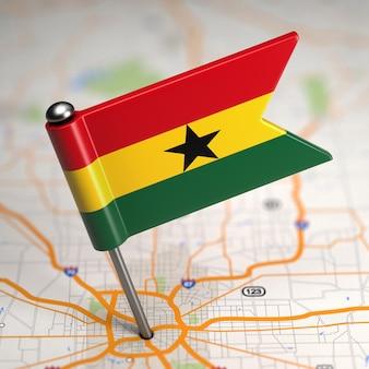 Piccola bandiera del ghana su uno sfondo di mappa con il fuoco selettivo.