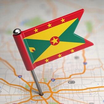 Piccola bandiera di grenada su uno sfondo di mappa con il fuoco selettivo.