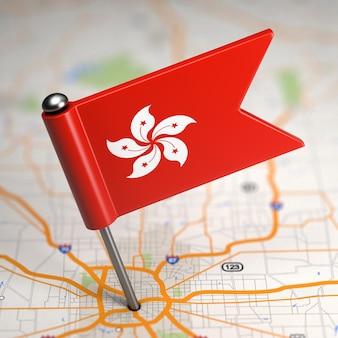 Piccola bandiera di hong kong su uno sfondo di mappa con il fuoco selettivo.