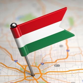 Piccola bandiera dell'ungheria su uno sfondo di mappa con il fuoco selettivo.
