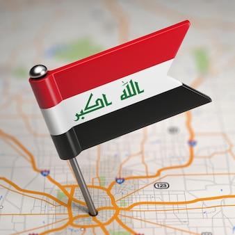Piccola bandiera dell'iraq su uno sfondo di mappa con il fuoco selettivo.