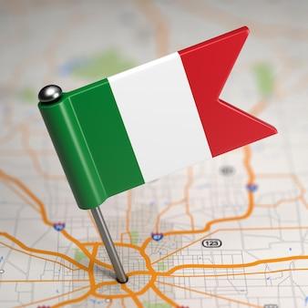 Piccola bandiera dell'italia incollata sullo sfondo della mappa con il fuoco selettivo.