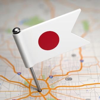 Piccola bandiera del giappone incollata sullo sfondo della mappa con il fuoco selettivo.