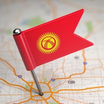 Piccola bandiera della repubblica del kirghizistan su uno sfondo di mappa con il fuoco selettivo.