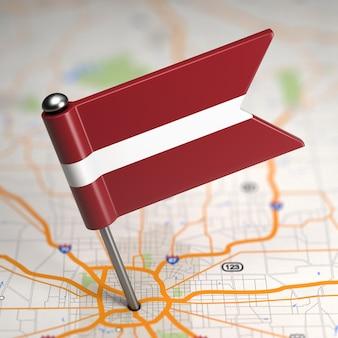 Piccola bandiera della lettonia incollata sullo sfondo della mappa con il fuoco selettivo.