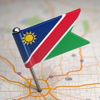 Piccola bandiera della namibia su uno sfondo di mappa con il fuoco selettivo.