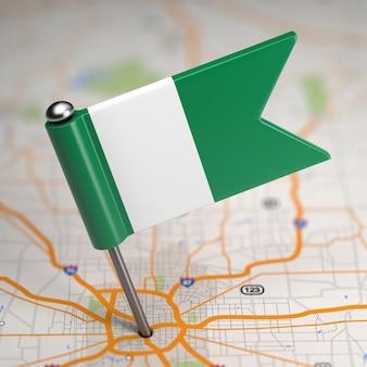 Piccola bandiera della nigeria su uno sfondo di mappa con il fuoco selettivo.