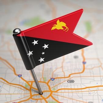 Piccola bandiera della papua nuova guinea su uno sfondo di mappa con il fuoco selettivo.