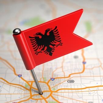 Piccola bandiera della repubblica d'albania incollata sullo sfondo della mappa con il fuoco selettivo.