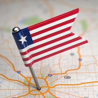 Piccola bandiera repubblica di liberia su uno sfondo di mappa con il fuoco selettivo.