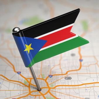 Piccola bandiera repubblica del sud sudan su uno sfondo di mappa con il fuoco selettivo.