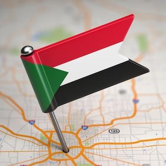 Piccola bandiera repubblica del sudan su uno sfondo di mappa con il fuoco selettivo.