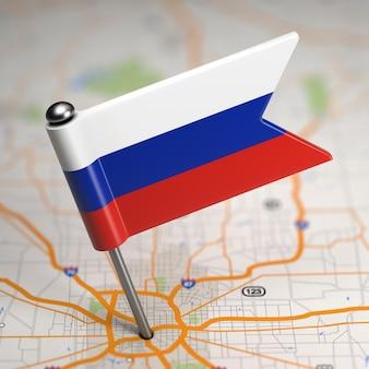 Piccola bandiera della russia incollata sullo sfondo della mappa con il fuoco selettivo.