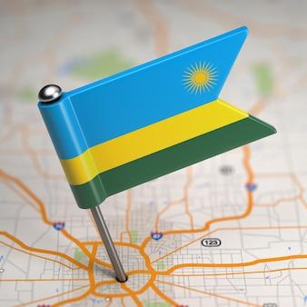 Piccola bandiera del ruanda su uno sfondo di mappa con il fuoco selettivo.