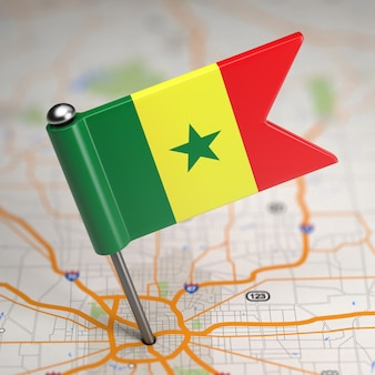 Piccola bandiera del senegal su uno sfondo di mappa con il fuoco selettivo.