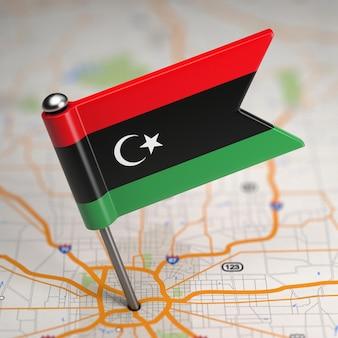 Piccolo stato di bandiera della libia su uno sfondo di mappa con il fuoco selettivo.
