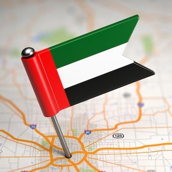 Piccola bandiera degli emirati arabi uniti incollata sullo sfondo della mappa con il fuoco selettivo.