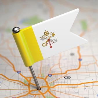 Piccola bandiera dello stato della città del vaticano su uno sfondo di mappa con il fuoco selettivo.