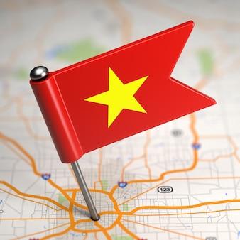 Piccola bandiera del vietnam incollata sullo sfondo della mappa con il fuoco selettivo.