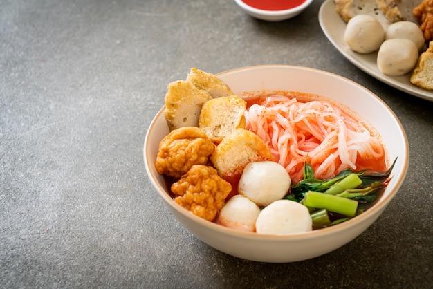 Piccoli spaghetti di riso piatti con polpette di pesce e polpette di gamberi in zuppa rosa, yen ta four o yen ta fo - stile asiatico