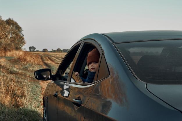 Un piccolo bambino spaventato guarda fuori dal finestrino aperto della macchina. viaggiare con i bambini.