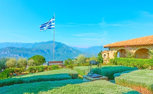 Piccolo giardino con bandiera greca sulla terrazza del monastero ortodosso di santo stefano a meteora, grecia