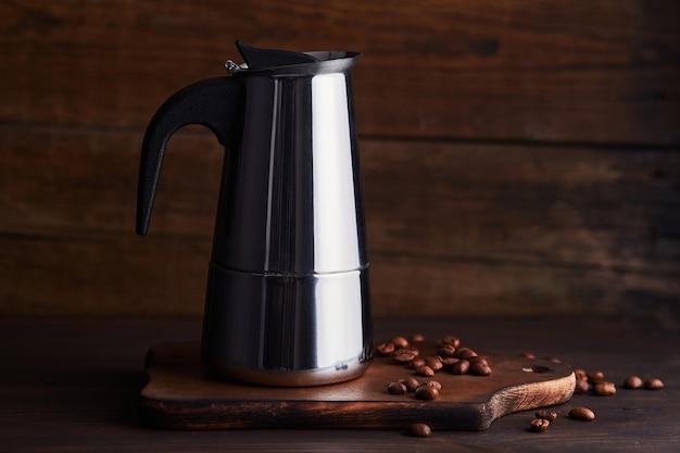 Piccola caffettiera geyser su fondo in legno. caffettiera in acciaio.
