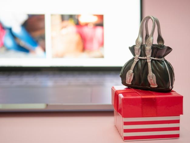 Confezione regalo piccola con borsa nera vicino al laptop
